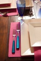 Place setting with square plates and cutlery with blue handles on pink table mat