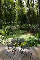 Wire mesh garden table and chairs on stone-flagged terrace with view of pond in woodland garden