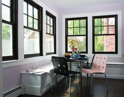 Colourful modern chairs and table in corner of room with black lattice windows