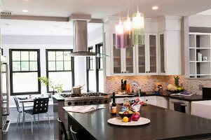 Free-standing kitchen island below modern pendant lamps with coloured glass shades