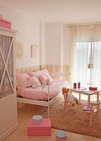 Charming girl's bedroom in pale pink with metal bed as sofa and teddy bear on child's table