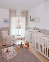 Elegant nursery with upholstered rocking chair, cot and changing unit in traditional, country-house style