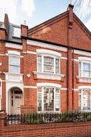 Old, English brick house with decorative, white window surrounds