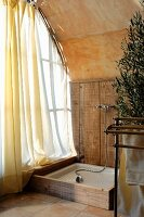 Rustic shower area in corner next to window with airy curtain and barrel vaulted ceiling