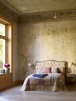 Scatter cushions on old-fashioned bed with bedside lamps in spacious art nouveau hotel room