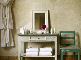 Washstand with mirror, toiletries, flowers, towels, dressing gown and chair in bathroom of Art Nouveau hotel