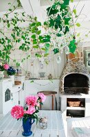 Vase of pink peonies on garden table in white wooden veranda with fireplace