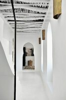 Hallway with Moroccan wooden roof structure and Moorish arch at far end