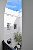 View from balcony of facade of Moroccan courtyard and section of blue sky