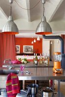 Industrial-style lamps above stainless steel sink unit; orange-painted walls and curtain partition in background