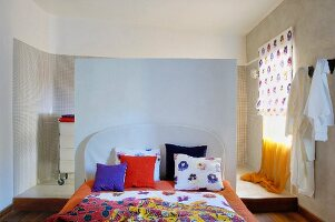 Floral-patterned linens on bed against half-height partition screening ensuite bathroom