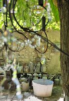 Zinc tubs and watering cans on floor against stone wall in vintage courtyard