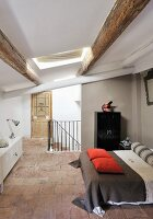 Open-plan sleeping area with double bed in renovated attic with wood-beamed ceiling in rustic interior