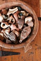 Small ceramic figurines in clay bowl on rustic wooden surface with metal fittings