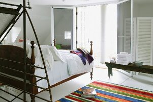 Modern, open-plan sleeping area with antique bed on partially visible striped rug opposite open double terrace doors