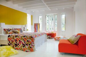 Shades of yellow and orange combined with white floor and wooden ceiling in bright, spacious retro bedroom