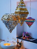 Party lanterns made of metal strips above glasses of champagne on low table and champagne bottles in a drift of confetti
