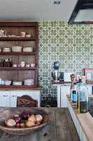 Wooden dish of onions on rustic table next to oil bottles on island counter in front of shelving against wall with patterned tiles