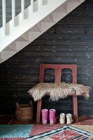 Sheepskin on chair and children's' boots against wooden wall in alcove below staircase