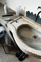 Concrete washstand with integrated, antique stone basin and minimalist outlet pipe