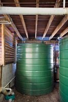 Water storage tanks in technology room of eco house; ceiling and walls made of wooden slats