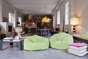 Lime green beanbag armchair and collection of different lamps in large, open-plan loft apartment