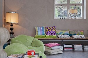 Collection of colourful cushions on wall-mounted bench, lime green beanbag chairs and postmodern table lamps contrasting with cool exposed concrete of loft interior