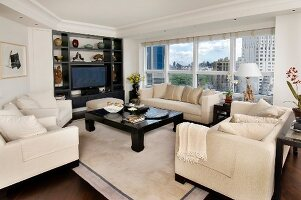 Sofa set with pale upholstery around dark wood coffee table in front of fitted shelving and panoramic window