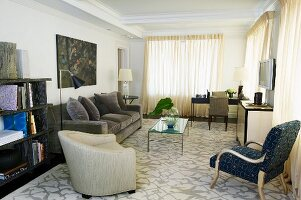Armchairs and grey sofa around glass table on patterned rug and closed curtains at windows