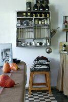 Kitchen utensils, tea caddies and crockery on wall-mounted shelves, tea towels on stool and pears on kitchen table