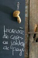 Handwritten menu and fresh penny bun mushroom hanging against blackboard in kitchen