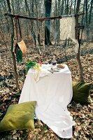 Gedeckter Tisch im Freien mit Gemüse und Gedeck; darüber an einem rustikalen Holzgestell hängende Fische