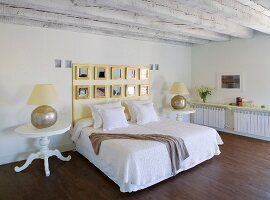 Simple double bed with framed mirrors on headboard flanked by traditional bedside tables in bedroom with wood beam ceiling