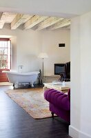 Free-standing vintage bathtub in modern living room with rustic, traditional ambiance