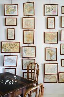 Pictures hung in vertical rows on wires and traditional wooden table and dark wood chairs