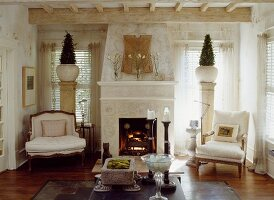 Open fireplace flanked by armchairs in front of decorative bushes in vases on columns against windows in country-style interior
