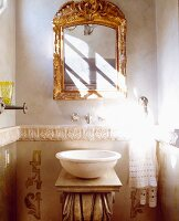 Antique stone basin on washstand below gilt-framed mirror in niche in bathroom with pattern of sunlight and shadow on wall