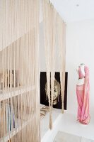String curtain in front of poster of Buddha in seating niche next to tailors' dummy dressed in Oriental belly dancer costume