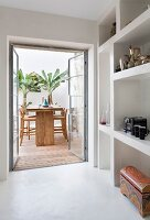 Collectors' items in large-scale fitted shelving beside terrace windows with view of seating area with wooden stools and banana trees