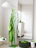 Housecoat hanging on a green metal clothes stand next to a wall mirror in the corner of a bedroom