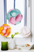 Decorations in window; spheres made from paper cake cases hung from ribbons