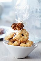 Small bags of biscuits decorated with miniature cake moulds as guest favours