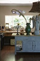 Angel statue next to green vase of flowering branches on vintage wooden sideboard in open-plan kitchen