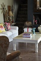 White-painted coffee table and sofa in rustic interior with foot of staircase