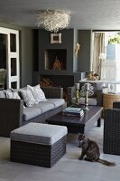 Grey wicker sofa set and coffee table in modern living room with birds'-nest ceiling lamp