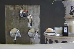 Designer, wall-mounted tap fittings on concrete panel and toiletries on vintage table
