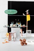 Retro lamp above modern dining table with glass top in front of black mural