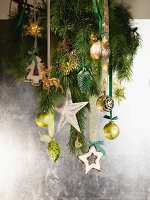 Fir branch with Christmas decorations hanging on silver wall