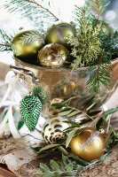 Christmas baubles and fir twigs in vintage copper bowl