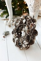 Wreath of pine cones and Christmas decorations leaning on chair leg on white wooden floor
